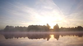Misty autumn morning on lake. Fog moving across still water stock video footage