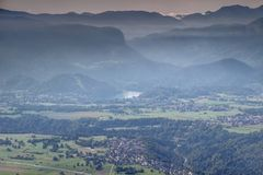 Misty autumn panorama of Lake Bled and surrounding mountains. Elevated view of Lake Bled, Breg village, Sava river, Babji Zob cliff, Bohinj range, Jelovica and Royalty Free Stock Image