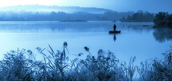 Misty blue morning, scenic lake. Blue tone lake at misty morning, one man fishing in a boat while standing. Reeds around lake and forest horizon royalty free stock photography