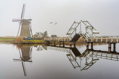 Misty and calm windmill bridge Royalty Free Stock Images