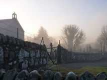 Misty church and graveyard Stock Image