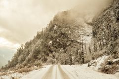Misty Cinematic mountain road landscape. Landscape with rocks, sunny day sky and clouds beautiful mountain asphalt road in winter stock images