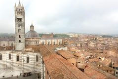 Misty city with historical buildings and roofs of the 14th century Duomo di Siena, Italy. UNESCO Heritage Site. Misty city with historical buildings and roofs of stock photography