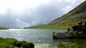 Misty cold morning after heavy rain at lake banks in Alpine mountains. Heavy dark clouds of mist stock video