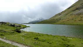 Misty cold morning after heavy rain at lake banks in Alpine mountains. Heavy dark clouds of mist stock video footage