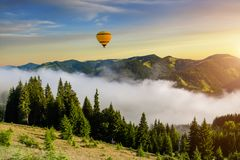 Misty dawn in the mountains in summer. Hot air balloon Stock Images