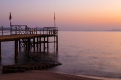 Misty dawn over the sea beach. Stairs to the sea Royalty Free Stock Photo