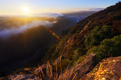Misty dawn over wooded mountains and river Royalty Free Stock Image