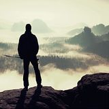 Misty day in rocky mountains. Silhouette of tourist with poles in hand. Hiker stand on rocky view point above misty valley. Royalty Free Stock Image