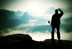 Misty day in rocky mountains. Silhouette of tourist with poles in hand. Hiker stand on rocky view point above misty valley. Silhouette of tourist with poles in Stock Photography