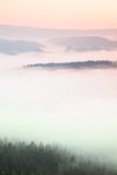 Misty daybreak in a beautiful hills. Peaks of hills are sticking out from foggy background, the fog is yellow and orange due to su Stock Photo