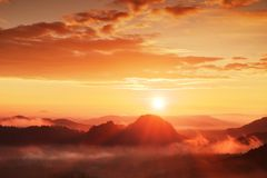 Misty dreamy landscape with autumn fog between hills and orange sky within early sunrise Stock Photos