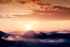 Misty dreamy landscape with autumn fog between hills and orange sky within early sunrise. Misty landscape with fog between hills and orange sky within early Royalty Free Stock Photography
