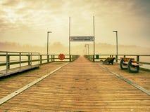 Misty dusk on the landmark fishing pier, pier railings. Wooden mole. Misty dusk on the landmark fishing pier, wooden pier railings. Wooden mole ends in thick stock image