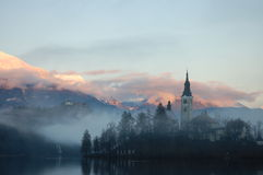Misty Evening. The Bled island church with the snowy mountains and the Bled castle in the background Royalty Free Stock Photos