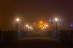 Misty Evening Footbridge. A walker pauses on a footbridge during a misty evening in Scarborough, North Yorkshire, UK royalty free stock photos