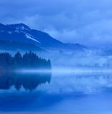 Misty evening on lake in mountains Stock Photography