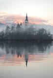 Misty Evening Reflection. The Bled island church reflecting in the water with the snowy mountains in the background Royalty Free Stock Photo