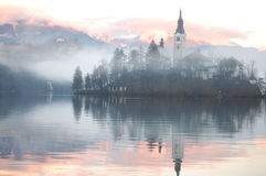 Misty Evening Reflection. The Bled island church reflecting in the water with the snowy mountains and the Bled castle in the background Royalty Free Stock Photos