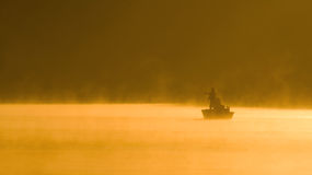 Misty Fishing Day on A Lake. One angler fishing on a misty sunlit lake Royalty Free Stock Photography