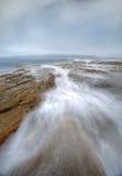 Misty fog and ocean chasm flows Stock Photos