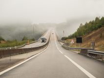 Misty foggy driving conditions in Normandy, France. Misty, foggy morning causing difficult driving conditions on a road trip driving across the Viaduct du Bec in Stock Images