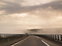 Misty foggy driving conditions in Normandy, France. Misty, foggy morning causing difficult driving conditions on a road trip driving across the Viaduct du Bec in Stock Photo