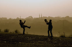 Misty hills children playing ball. Foggy day, hill kids playing ball, rear view looks istanbul houses and mosques Stock Images