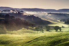 Misty hills and meadows in Tuscany at sunrise Royalty Free Stock Images