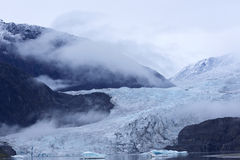 Misty hues of Mendenhall Glacier. Misty hues of blue of the receding tongue of the Mendenhall Glacier and its ice melt lake in Juneau, Alaska royalty free stock photo