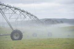 Misty Irrigation pelo sistema de extinção de incêndios do pivô no campo de grama Fotos de Stock Royalty Free