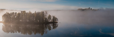 Misty Island. An island in a mist covered lake. Sodermanland, Sweden royalty free stock image