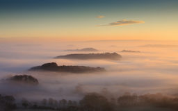 Misty Islands. Landscape view showing successive line of tree-topped hills emerging from a thick layer of radiation fog, Bridport, Dorset, England Stock Image
