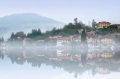 Misty Italian village. Italian village reflected in the lake in the morning mist Stock Photography