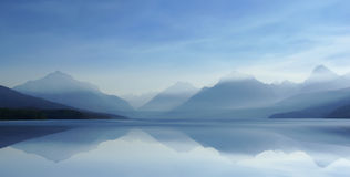 Misty Lake H 8-07. Beautiful distant mountain peaks rise through morning mist and are reflected in a calm lake Royalty Free Stock Images