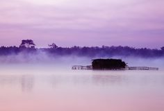Misty lake and huts Stock Photo