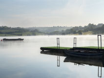 The misty lake. Mist over a calm lake with boats Stock Photos