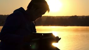 Misty lake and a woman looking at photo album at sunset in slo-mo stock footage