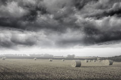 Misty landscape with bales of straw Stock Photography