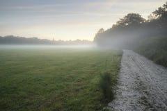 Misty landscape during sunrise in English countryside landscape Royalty Free Stock Photo