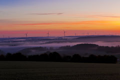 Misty Landscape. Sunset landscape with tree silhouette and windmills in Fog Stock Photos