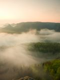 Misty melancholic morning. View into long deep valley full of fresh  spring mist. Landscape within daybreak after rainy night Stock Photo