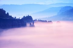 Misty melancholy daybreak in beautiful fairy valley. Peaks of rock trim creamy foggy clouds Stock Photo