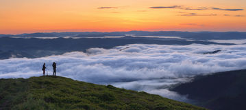 Misty morning. A photographers takes pictures fog from the top of mountain Stock Photography