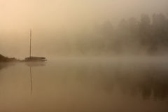 Misty morning boat at the lake Stock Images