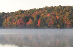 Misty Morning on Burr Pond. Fall foliage reflecting off of the misty waters of Burr Pond State Park in Torrington Connecticut in Autumn Stock Photography