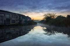 Misty Morning on the canal. Mist rising up of the water, on a canal in Cape Town City, South Africa. The canal has tree foliage on one side and suburban houses royalty free stock photos