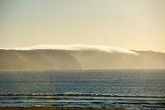 Misty morning clouds over coastal cliff Royalty Free Stock Photo