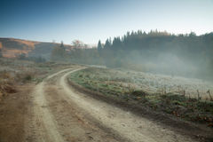 Autumnal morning on a dirt road Stock Photo