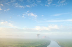 Misty morning on Dutch farmland with windmill Royalty Free Stock Photo